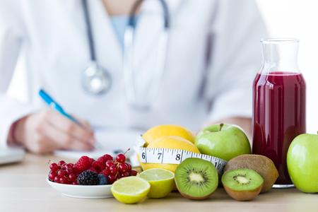 栄養価のテーブルにリンゴ、キウイ、レモン、ベリーなどのいくつかの果物のクローズアップ。