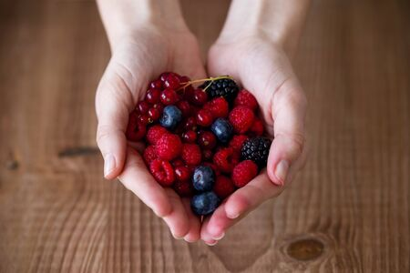 Close-up of some hands holding blueberries and raspberries over wooden background. Stok Fotoğraf - 98593168