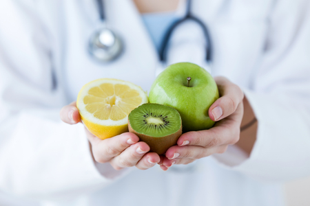 Close-up of doctor hands holding fruit such as apple, kiwi and lemon. Stock Photo