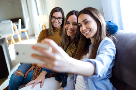 Portrait of three happy beautiful women taking a selfie and enjoying time together at home.