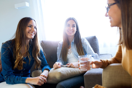 Portrait of three happy beautiful women talking and laughing at home.