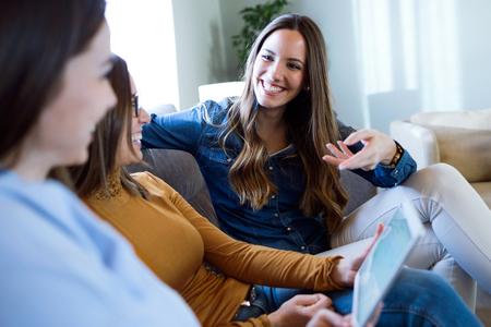 Portrait of three happy beautiful women using digital tablet at home.