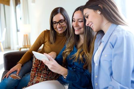 Portrait of three happy beautiful women using smartphone at home. Stock Photo
