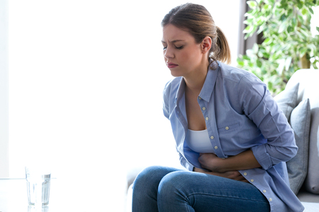 Shot of unhealthy young woman with stomachache leaning on the couch at home.