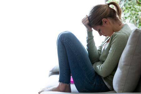 Tir de malheureuse solitaire déprimé jeune femme assise sur le canapé à la maison. dépression concept Banque d'images - 99394588