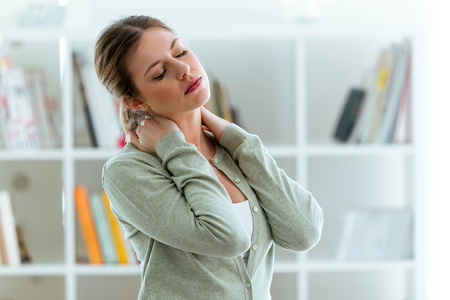 Shot of tired young woman with neck pain at home. Imagens