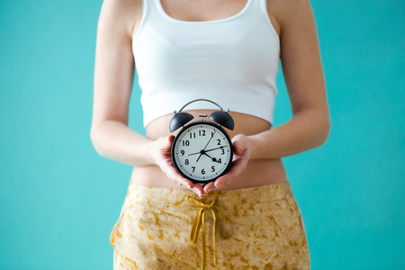 Close-up of a young woman holding a clock over blue background.
