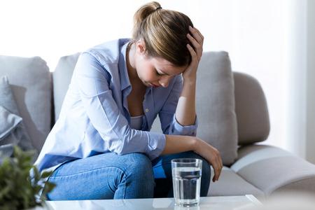 Tir de malheureuse solitaire déprimé jeune femme assise sur le canapé à la maison. dépression concept Banque d'images - 99394590