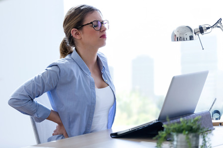 Shot of tired young woman with back pain using her laptop at home.