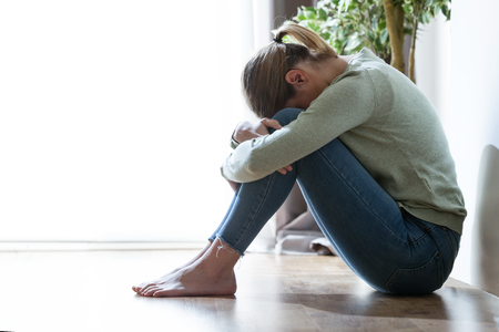 Shot of unhappy lonely and depressed young woman hiding her face between legs at home.