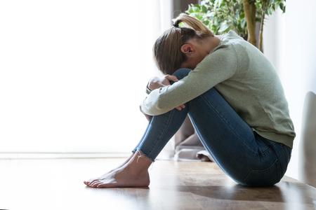 Ujęcie nieszczęśliwej samotnej i przygnębionej młodej kobiety ukrywającej twarz między nogami w domu. Zdjęcie Seryjne