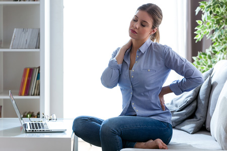 Shot of tired young woman with shoulder and back pain sitting on the couch at home. Stockfoto