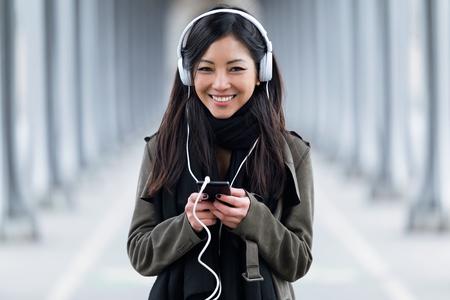 음악을 듣고 거리에서 카메라를보고 웃는 아시아 젊은 여자의 초상화. 스톡 콘텐츠 - 99894815