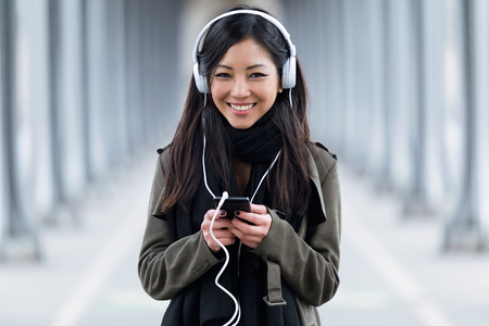 Portrait of smiling asian young woman listening to music and looking at camera in the street.