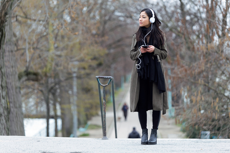 Shot of pretty asian young woman listening to music with her smartphone in the street. Stock Photo