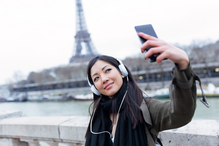 Shot of pretty asian young woman taking a selfie in front of Eiffel tower in Paris while listening to music. 写真素材 - 99894838