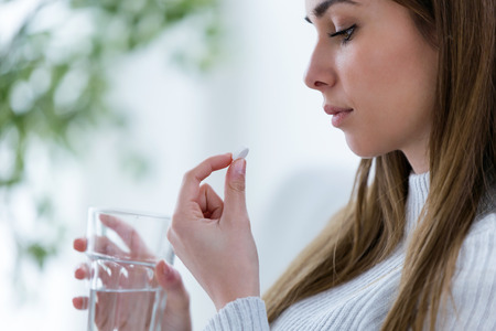 Shot of depressed young woman holding pill and glass of water while looking this at home.