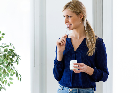 Shot of beautiful young woman looking sideways while eating yogurt at home. Stock Photo