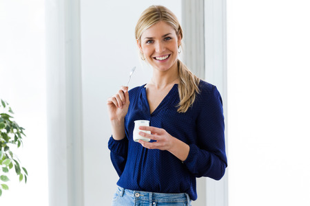 Portrait of beautiful young woman looking at camera while eating yogurt at home. Zdjęcie Seryjne