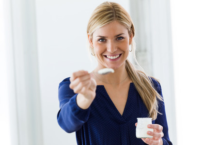 Portrait of beautiful young woman looking at camera while eating yogurt at home. Stok Fotoğraf