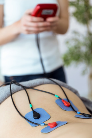 Shot of young physioterapist applying electro stimulation in physical therapy to a patient in physio room.