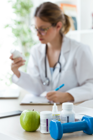 Shot of female dietician holding a nutritional supplement while writing the properties in the consultation. Stock fotó