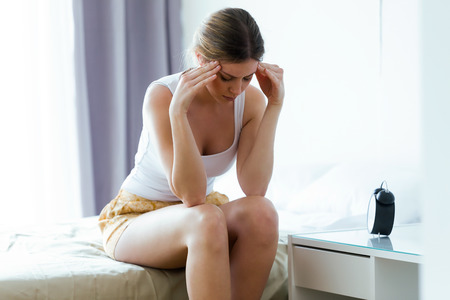 Shot of unhappy lonely depressed young woman sitting on bed at home. Depression concept.
