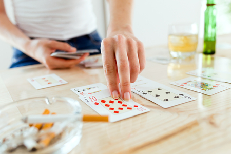 Close-up of the hands of a woman playing poker. Addiction concept.