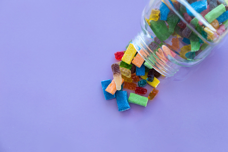 Close-up of colorful jelly candies in a bottle. Addiction concept.