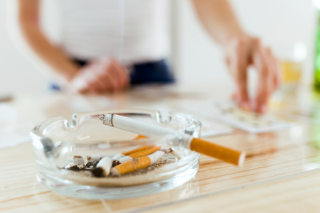 Close-up of cigarette in ashtray. On the background, woman playing with cards.
