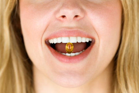 Close-up of a woman with a pill in her mouth. Addiction concept. Stock Photo - 101982840