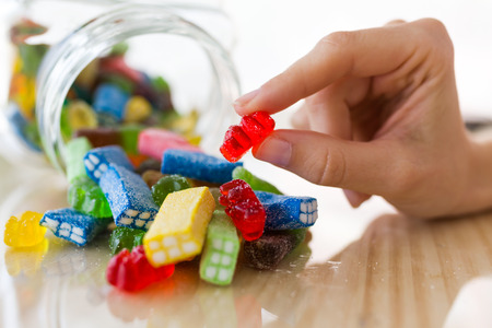 Close-up of the hand of young woman taking colorful jelly candies. Stockfoto