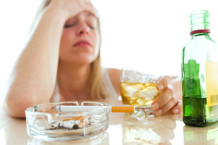Shot of depressed young woman drinking glass of whiskey and smoking at home. Stock Photo