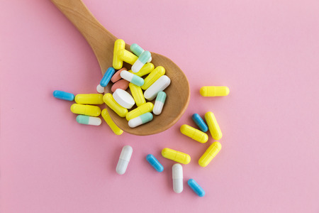 Close-up of a spoon full of pills on pink background. Addiction concept.