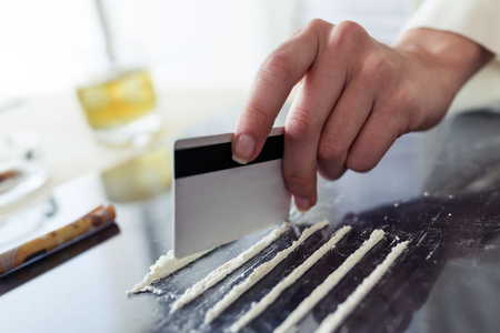 Close-up of hands of young druggie is doing tracks of cocaine with a credit card on the table. Stock Photo