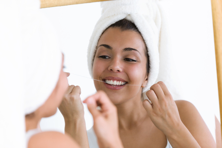 Shot of pretty young woman using dental floss in a home bathroom.