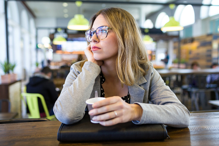 Shot of pretty young woman looking sideways while drinking cup of coffee at cafe. Stockfoto