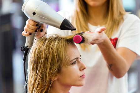 Shot of hairdresser drying female customer's hair in beauty salon. Stock fotó
