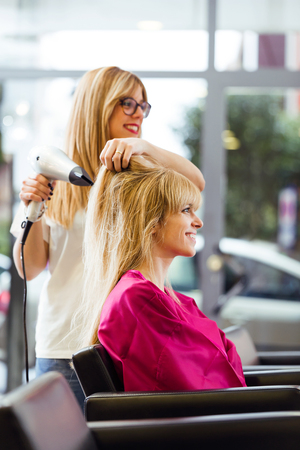 Shot of hairdresser drying female customer's hair in beauty salon. Stock Photo