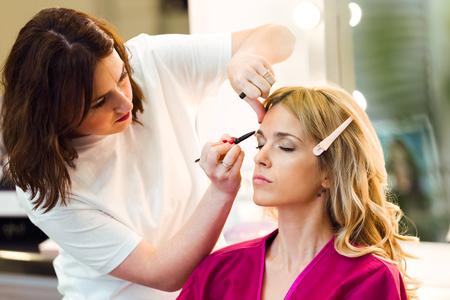 Plan d'une maquilleuse faisant du maquillage belle femme dans le salon de beauté. Banque d'images