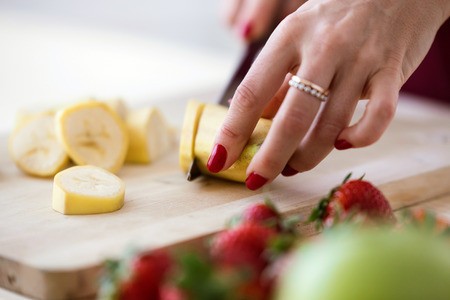 Close-up of the hands of a woman cutting banana on the wooden board.