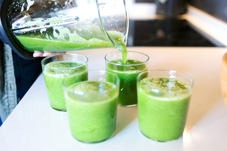 Close-up of woman serving detox green juice into glasses at home. Stock Photo
