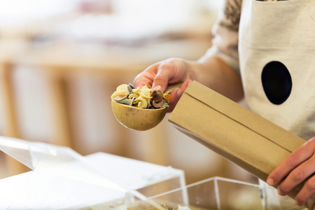 Close-up of a saleswoman taking pasta from a shopping bag in an organic store.