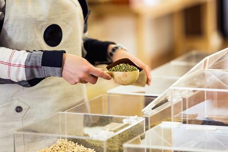 Gros plan d'une vendeuse mettant le soja dans un sac à provisions en vrac dans un magasin bio