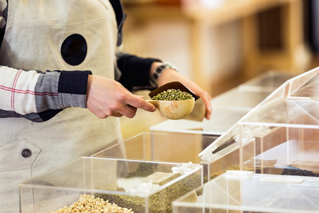 Primo piano della commessa che mette la soia in una borsa della spesa all'ingrosso in un deposito biologico.
