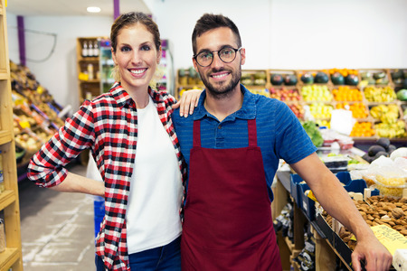 Portrait of attractive young sellers looking at camera in health grocery shop. Stock Photo