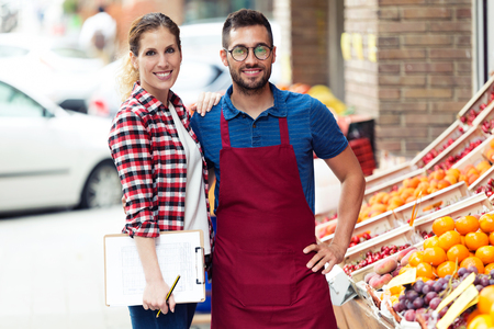 Portrait of beautiful young sellers looking at camera in health grocery shop. Stock Photo