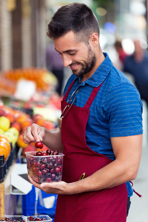 Shot of handsome young salesman holding cherries box in health grocery shop