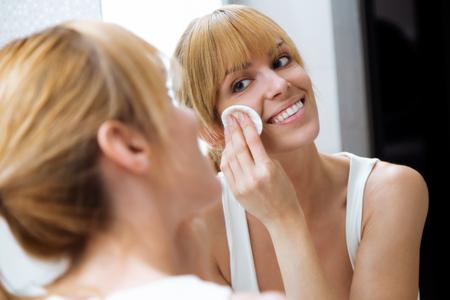 Foto de hermosa mujer joven quitando maquillaje junto al espejo en casa.