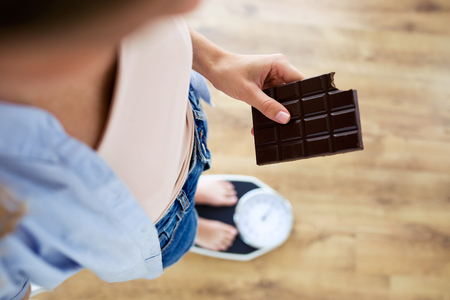 Close-up of young woman holding chocolate bar on a weigh scale at home.